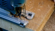 Man sawing plank electric fretsaw close-up video