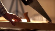 A man sawing wood Board with hand saw. Closeup. Slow motion video