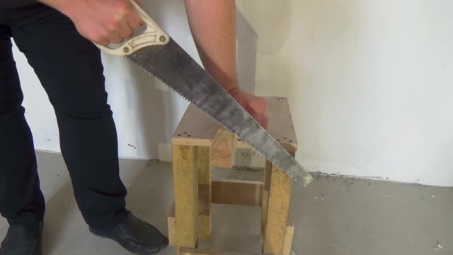A man saws a pine beam. Use of a hand saw. Work at the construction site. The joiner makes the workpieces of wood video