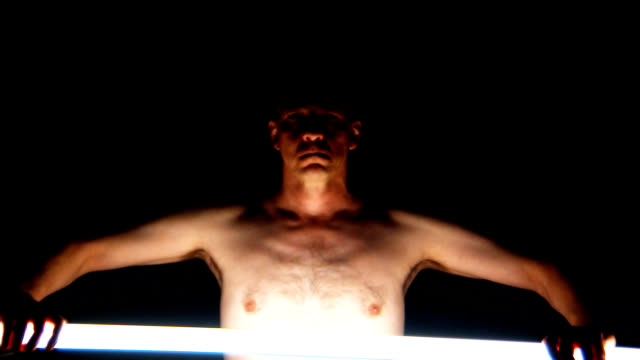 Man scanning  himself with illuminated bar, performance video