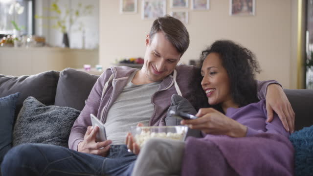 DS Man scrolling on his phone while watching TV with his girlfriend video