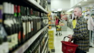 Man searching for a good wine in supermarket video