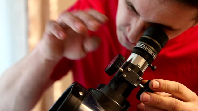 man sets up a telescope video