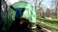 man shake out compost from wheelbarrow into eco greenhouse video