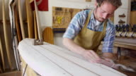 Man Shaping Custom Surfboard In Workshop Shot On RED Camera video