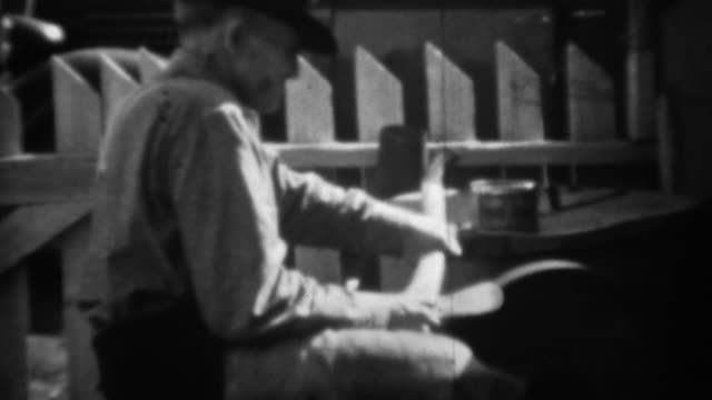 1936: Man sharpening axe on foot powered stone wheel grindstone. video
