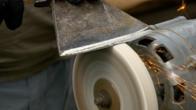 A man sharpens a big ax close-up video