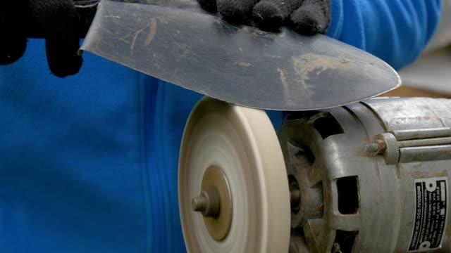 A man sharpens a shovel Work on a sharpening machine. video