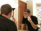 Man shaves face in front of mirror video