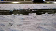 Man shovel away snow, legs view, night time, road traffic on background video