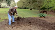man shoveling dirt and showing back pain video