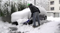 Man shoveling snow in front of his car video