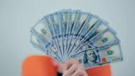 Man showing hundred dollar bills. Winks at final video