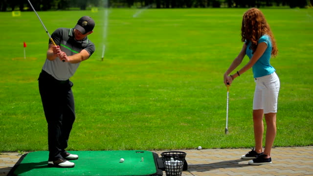 Man shows girl how to hit the ball in golf video