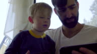 Man shows little boy a game on a cell phone video