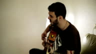 A man singing emotionally and accompanying himself with a guitar. video