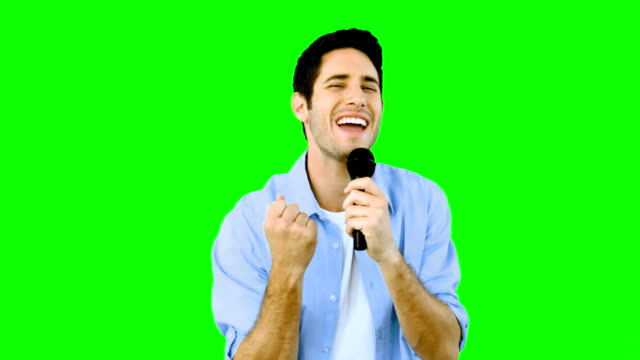 Man singing into microphone with emotion on green screen video
