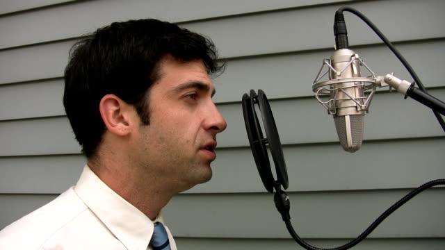 Man sings to microphone. video