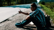 Man sit at road in countryside. Hitchhiking. Thumb up. Smoking cigarette video
