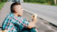 Man sit at road in countryside. Hitchhiking. Waiting. Eating banana. Sunny day video