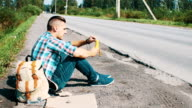 Man sit at road in countryside. Hitchhiking. Waiting for help. Eating banana video