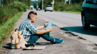 Man sit at road in countryside. Hitchhiking. Waiting for help. Looking map video