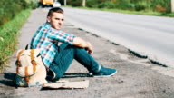 Man sit at road in countryside. Hitchhiking. Waiting for help. Take smartphone video