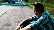 Man sit at road in countryside. Hitchhiking. Waiting. Smoking cigarette video