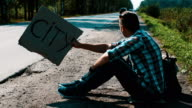 Man sit at road in countryside with cardboard plate sign city. Hitchhiking video