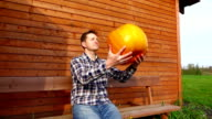 Man sit near wooden house, throw up and catch orange pumpkin video