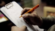 Man sit underline words in list, put ticks on sheet of paper in folder by pen video