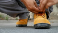 Man siting to wears safety shoes video