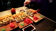 Man sits at the table in restaurant and eats japanese food video
