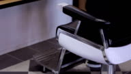 A man sits down on a barber chair in a barbershop video