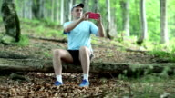 Man sits on a fallen tree in the forest and makes photos on his smartphone video