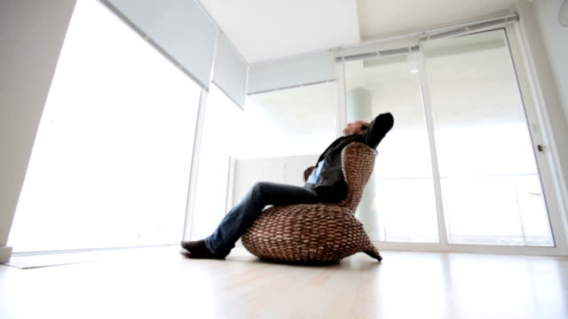 Man sits relaxing in an empty apartment video