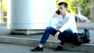 man sitting and talking with smartphone on the street video