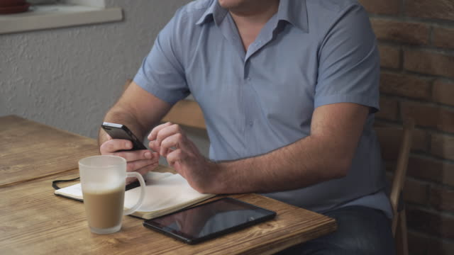 A man sitting at a desk with a phone in his hand, lies next to the tablet and notebook video