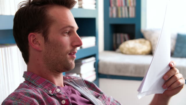 Man Sitting At Desk In Home Office Reading Document video