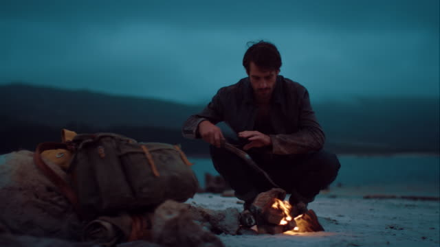 Man sitting at warm campfire video