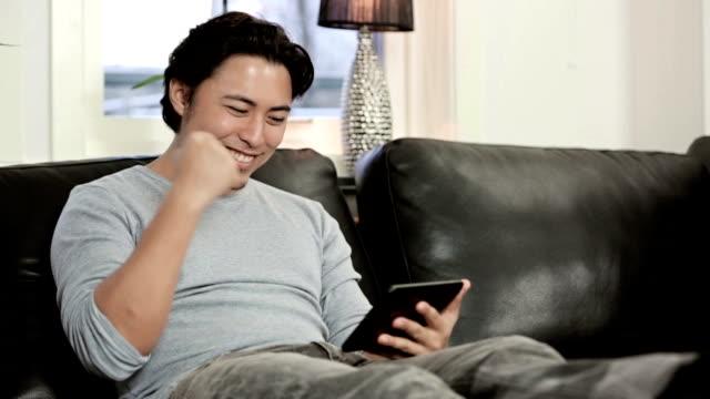 Man sitting down in living room swiping his digital tablet video
