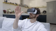 Man sitting down on the sofa wearing VR glasses video