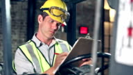 Man sitting in forklift looking at clipboard video