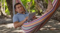 Man sitting in hammock using digital tablet video