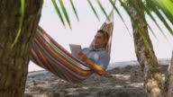 Man sitting in hammock using laptop computer video