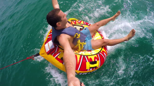 Man sitting in inflatable ring towed by a boat in the water and recording himself with Go Pro camera video