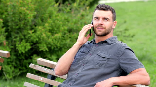 Man sitting in park, talking on mobile phone video