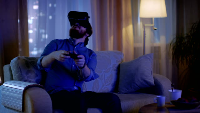 Man Sitting on a Couch in His Living Room  Plays Video Games on His Console While Wearing Virtual Reality Headset. video