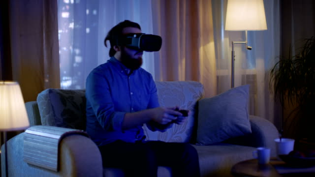 Man Sitting on a Couch in His Living Room Wearing  Plays Video Games on His Console While Wearing Virtual Reality Headset. video