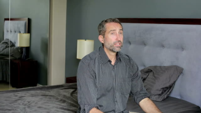 man sitting on bed and looking distressed video